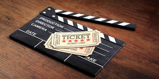 Cinema old type tickets beige isolated on a movie clapper and a wooden background, 3d illustration. Stock Photography