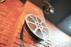 Of vintage film reel and strips hangs on a brick wall. 35 mm film reel royalty free stock images