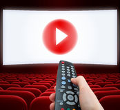 Cinema screen with play media button in center and remote control in hand Royalty Free Stock Photography