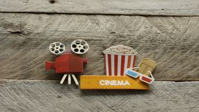 Cinema sign with popcorn bucket movie projector on wood background. Tub of popcorn with a cinema sign with 3d glasses and projector on a wood background with stock image