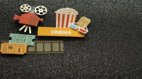 Cinema sign with popcorn bucket movie tickets on film strip all on black sparkled background. Tub of popcorn with a cinema sign with 3d glasses and projector stock photo