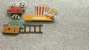 Cinema sign with popcorn bucket movie tickets on film strip on silver sparkled background. A Tub of popcorn with a cinema sign with 3d glasses and movie tickets royalty free stock photography