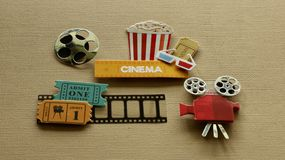 Cinema sign with popcorn tub 3d glasses movie tickets projector on tan background. Tub of popcorn with a cinema sign with 3d glasses movie tickets on film strip royalty free stock photography
