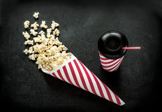 Cinema snacks - cornet popcorn and drink on black Stock Photos