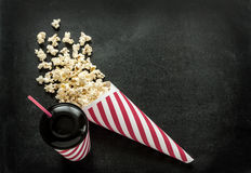 Cinema snacks - cornet popcorn and drink on black Stock Photography
