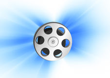Cinema spool. In blue rays background Royalty Free Stock Photos