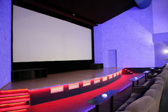 Cinema stage. Empty blue cinema auditorium with line of sofa and tables, red stage and projection screen. Side view. Ready for adding your own picture Royalty Free Stock Photography