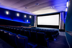 In the cinema theater. Dark blue auditorium in cinema theater. The white screen in foreground. Empty new seats Royalty Free Stock Images