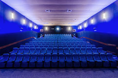 In the cinema theater. Dark blue auditorium in cinema theater. The white screen in foreground. Empty new seats Royalty Free Stock Image