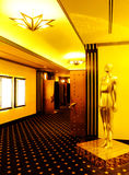 Cinema theatre lobby. An interior shot of a cinema movie house lobby or foyer, with grand golden color decor and finishing. Ceiling light in shape of large gold stock photography