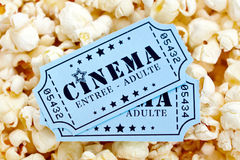 Cinema tickets and popcorn. Pair of French cinema tickets on popcorn background Royalty Free Stock Photos