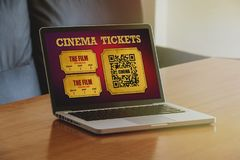 Cinema tickets purchase in a laptop screen on a wooden table. Stock Photo
