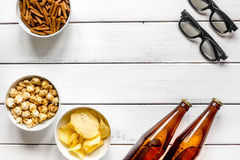 Cinema and TV whatching with beer, crumbs, chips and pop corn white wooden background top view mock-up. Cinema and TV whatching with beer, crumbs, chips and pop Royalty Free Stock Images