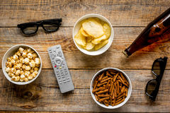 Cinema and TV whatching with beer, crumbs, chips and pop corn wooden background top view. Cinema and TV whatching with beer, crumbs, chips and pop corn on wooden Royalty Free Stock Image