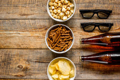 Cinema and TV whatching with beer, crumbs, chips and pop corn wooden background top view mock-up. Cinema and TV whatching with beer, crumbs, chips and pop corn Stock Photos