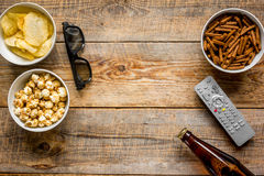 cinema and TV whatching with beer, crumbs, chips and pop corn wooden background top view mock-up royalty free stock image