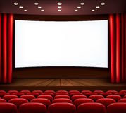 Cinema with white screen, curtain and seats. Stock Photos