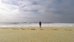 Cinemagraph ändlös längd i fot räknat En ung kvinna står på havkusten arkivfilmer