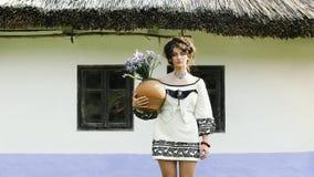 Cinemagraph - ένα ουκρανικό κορίτσι στέκεται κοντά σε μια ουκρανική καλύβα απόθεμα βίντεο