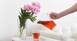 Cinemagraph 妇女的手藏品玻璃水瓶和倾吐的新莓果饮料到里 股票录像
