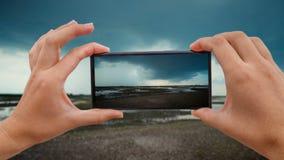 Cinemagraph av att ta det mobila fotoet av landskapet med åskmoln stock video