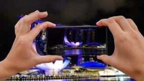Cinemagraph av att ta det mobila fotoet av Marina Bay Sands på natten lager videofilmer