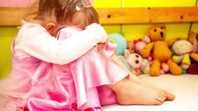 Cinemagraph av gulligt liten flickasammanträde på mycket olycklig säng arkivfilmer