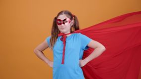 Cinemagraph - beautiful girl dressed as superhero. Over yellow background. The cloak is moving in loop stock footage