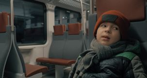 Boy in moving commuter train at night stock footage