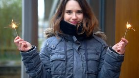 Cinemagraph de femme dehors dans le froid tenant deux cierges magiques