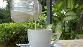 Cinemagraph de la leche de colada en la taza blanca almacen de video