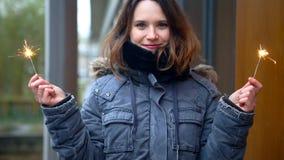 Cinemagraph de la mujer afuera en el frío que sostiene dos bengalas