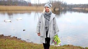Cinemagraph de la mujer que se coloca delante del lago con un ramo de flores almacen de metraje de vídeo
