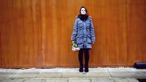 Cinemagraph de la mujer que se coloca en la pared de madera con el ramo de rosas almacen de video