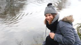 Cinemagraph de la mujer sonriente por una natación del lago y del pato cerca almacen de metraje de vídeo