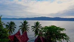 Cinemagraph de lac toba en Sunny Weather avec les toits traditionnels de style de Batak de l'île de Samosir, Sumatra du Nord clips vidéos