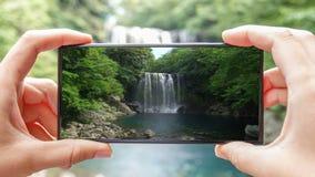 Cinemagraph de tomar la foto de la cascada de Cheonjeyeon en Corea del Sur de la isla de Jeju con el teléfono móvil Turismo activ metrajes