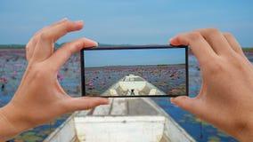 Cinemagraph de tomar la foto móvil de montar el barco de madera de Longtail entre Lotus Flowers roja Front View en Thale Noi almacen de metraje de vídeo