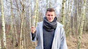 Cinemagraph del hombre hermoso en el bosque que sostiene una bengala