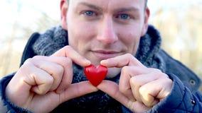 Cinemagraph del hombre rubio que lleva a cabo un pequeño corazón del centelleo