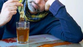 Cinemagraph dell'uomo esaurito che si siede alla tavola con vetro di tè video d archivio