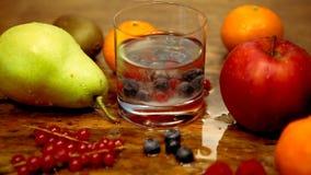 Cinemagraph della tavola con i frutti e del bicchiere d'acqua con zucchero di versamento stock footage