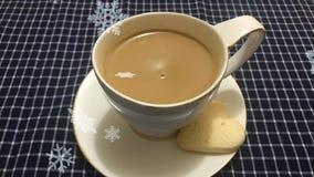 Cinemagraph - der Edschnee, der auf den weißen Tasse Kaffee mit Herzen fällt, formte Plätzchen auf einer Tabelle mit einer karier lizenzfreie abbildung