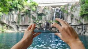 Cinemagraph des Machens des Fotos Cheonjeyeon-Wasserfalls auf Jeju-Insel Südkorea mit Handy Aktiver Tourismus herein stock footage