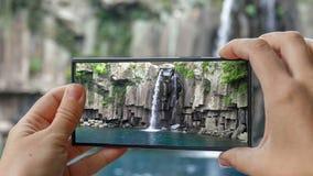 Cinemagraph des Machens des Fotos Cheonjeyeon-Wasserfalls auf Jeju-Insel Südkorea mit Handy Aktiver Tourismus herein stock video footage
