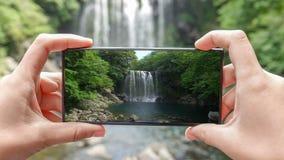 Cinemagraph des Machens des Fotos Cheonjeyeon-Wasserfalls auf Jeju-Insel Südkorea mit Handy Aktiver Tourismus herein stock video