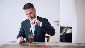 Cinemagraph do homem de negócios que senta-se na tabela e no chá bebendo video estoque