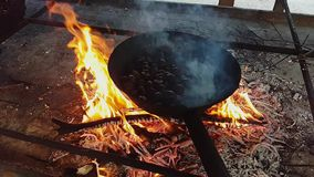 Cinemagraph effect with steaming chestnuts in the pan. And still fire background stock footage