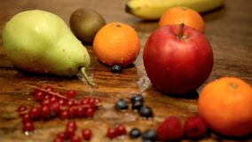 Cinemagraph of fresh fruits and berries on wet wooden table. Cinemagraph of fresh fruits and berries on wet rustic wooden table stock footage