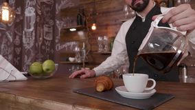 Cinemagraph gently filling a cup of fresh brewed coffee on a tray with a fresh croissant. Elegant bar and nice looking barista stock video footage